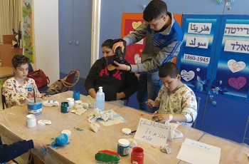 Palestinian patient Mohamad Abdeen taking photos of the children painting the stones