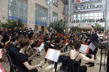 French orchestra plays in Atrium 5 viewers from balcony red